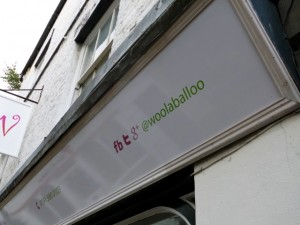 Using a shop sign to promote social media at Hexham's Woolaballoo (10 Sep 2012). Photograph by Graham Soult